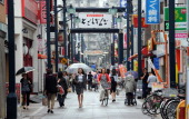 Pedestrians walk through the Togoshi shopping district in Tokyo on October 1 2013 Japan's prime minister vowed on October 1 to press ahead with a...