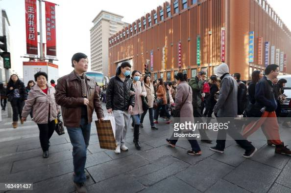 Pedestrians walk through the Wangfujing shopping district of Beijing China on Sunday March 10 2013 China's industrial output had the weakest start to...