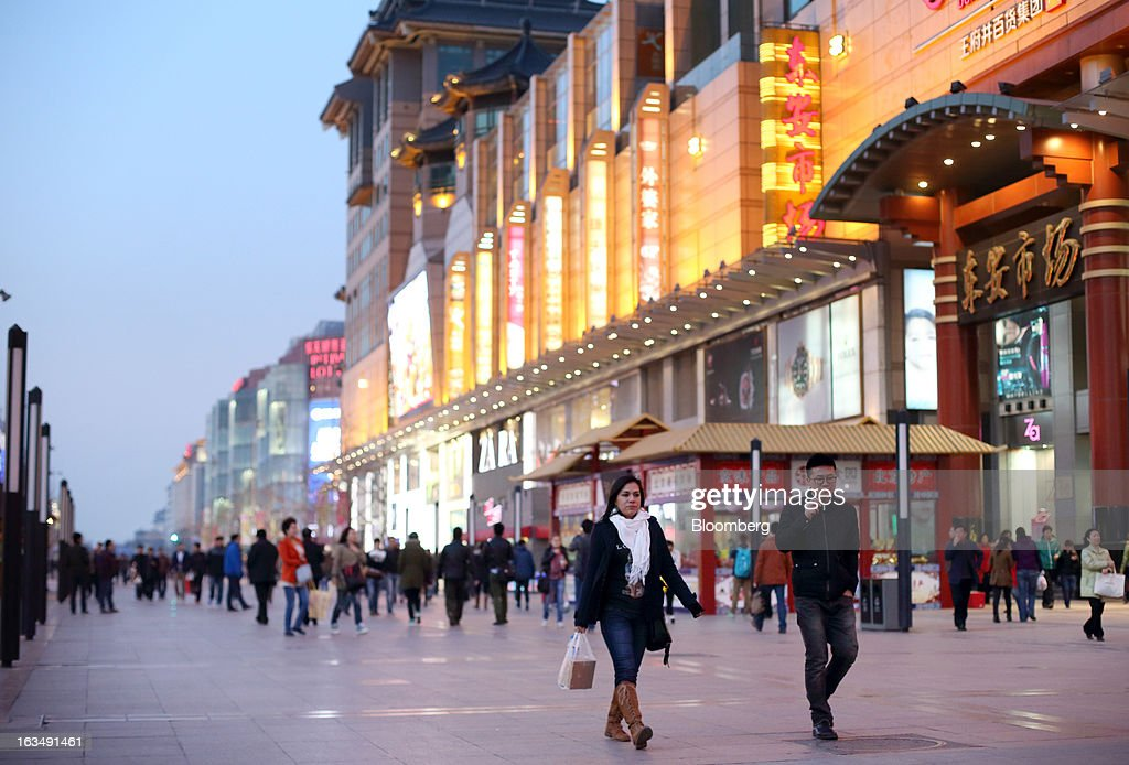 Pedestrians walk through the Wangfujing shopping district of Beijing, China, on Sunday, March 10, 2013. China's industrial output had the weakest start to a year since 2009 and lending and retail sales growth slowed, toughening challenges for a new leadership that wants to narrow the gap between rich and poor. Photographer: Tomohiro Ohsumi/Bloomberg via Getty Images