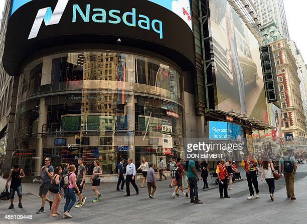 Pedestrians walk through Times Square in front of the Nasdaq Stock Market August 24 2015 in New York US stocks opened down more than five percent...