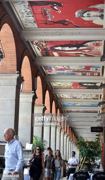 Pedestrians walk under the City Hall Arcade in Toulouse on August 19 which is decorated by works of the painter Raymond Moretti The 29 paintings...