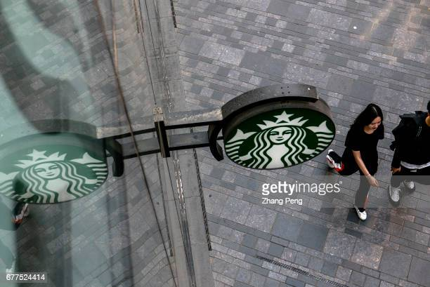 Pedestrians walk under the logo of Starbucks Since June 1st 2017 the fulltime employees of Starbucks in Chinese market who have worked for two years...