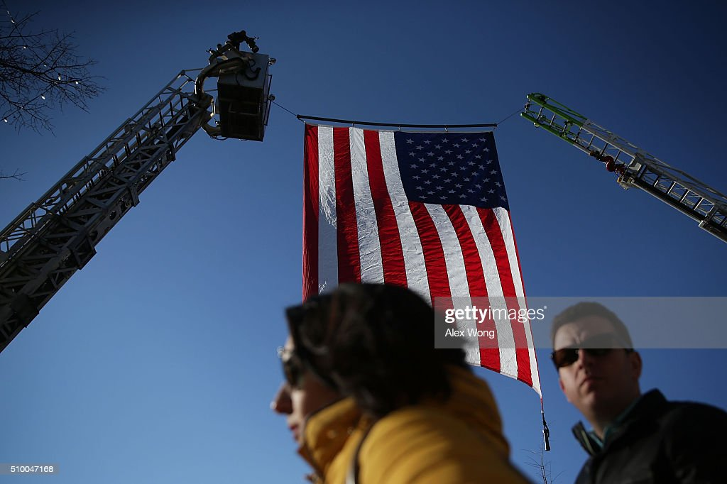 Pedestrians walk underneath a U.S. flag prior to a CBS News GOP Debate February 13, 2016 outside the Peace Center in Greenville, South Carolina. Residents of South Carolina will vote for the Republican candidate at the primary on February 20.