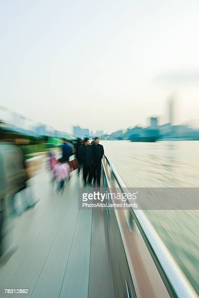 Pedestrians walking by riverside, blurred motion