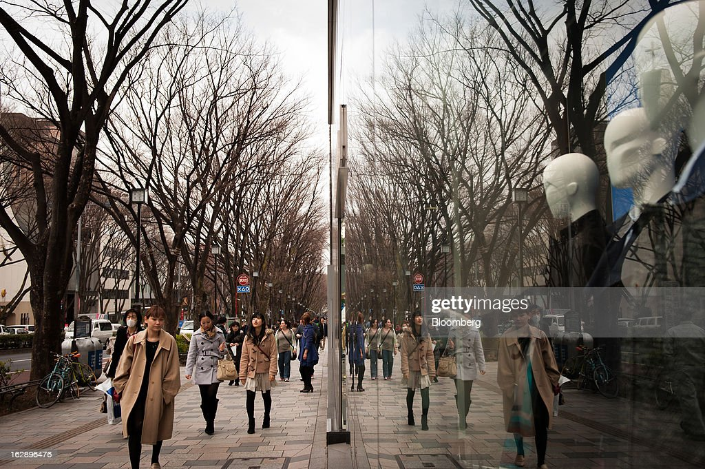 Pedestrians walking down a street are reflected in a store window in the shopping district of Omotesando in Tokyo, Japan, on Friday, March 1, 2013. Japan's consumer prices fell for the eighth time in nine months, highlighting the challenges facing the Bank of Japan in reaching a 2 percent inflation target. Photographer: Noriko Hayashi/Bloomberg via Getty Images