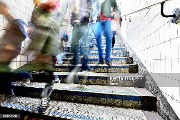 Pedestrians walking down the subway station stairs