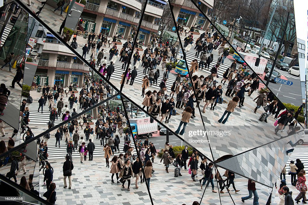Pedestrians walking on the street are reflected in patterned mirrored glass on the facade of a mall in the shopping district of Omotesando in Tokyo, Japan, on Friday, March 1, 2013. Japan's consumer prices fell for the eighth time in nine months, highlighting the challenges facing the Bank of Japan in reaching a 2 percent inflation target. Photographer: Noriko Hayashi/Bloomberg via Getty Images