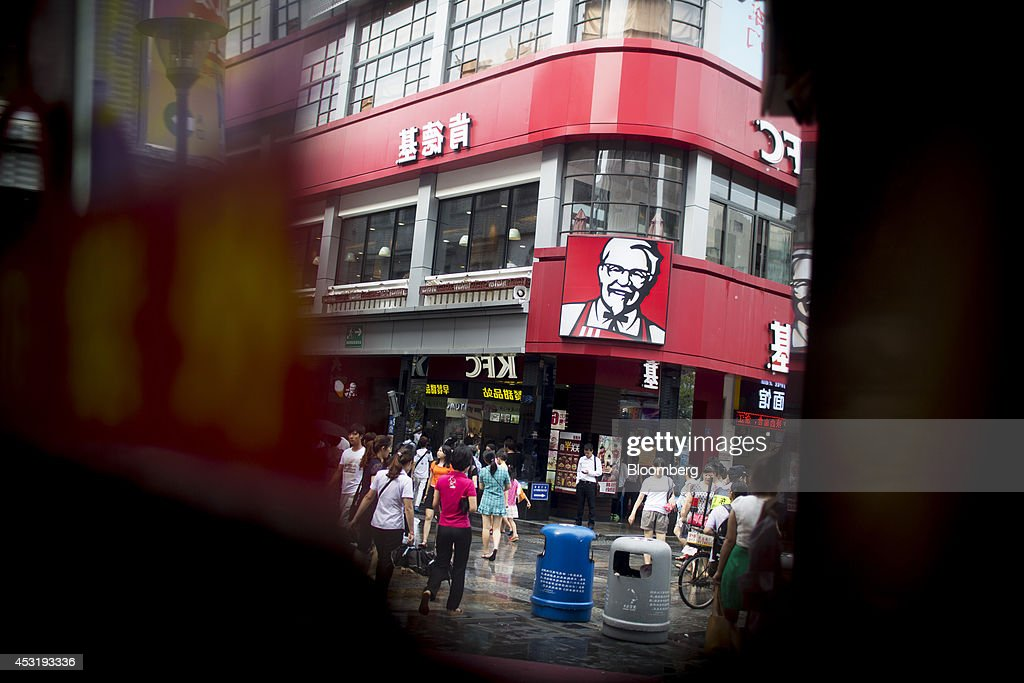 Pedestrians walking past a KFC restaurant, operated by Yum! Brands Inc., are reflected in a mirror in the pedestrianized Dongmen area of Shenzhen, China, on Monday, Aug. 4, 2014. Yum, owner of KFC and Pizza Hut, said its China team is trying to regain customers after a supply chain scare has recently hurt results. Photographer: Brent Lewin/Bloomberg via Getty Images