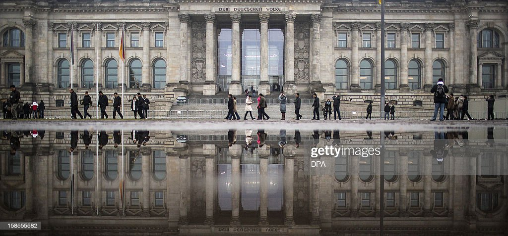 Pedestrians walking past the Reichstag building reflect in a puddle on December 19, 2012 in Berlin. The Reichstag houses the Bundestag, lower house of parliament. AFP PHOTO / HANNIBAL HANSCHKE GERMANY OUT