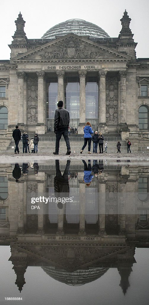 Pedestrians walking past the Reichstag building reflect in a puddle on December 19, 2012 in Berlin. The Reichstag houses the Bundestag, lower house of parliament.
