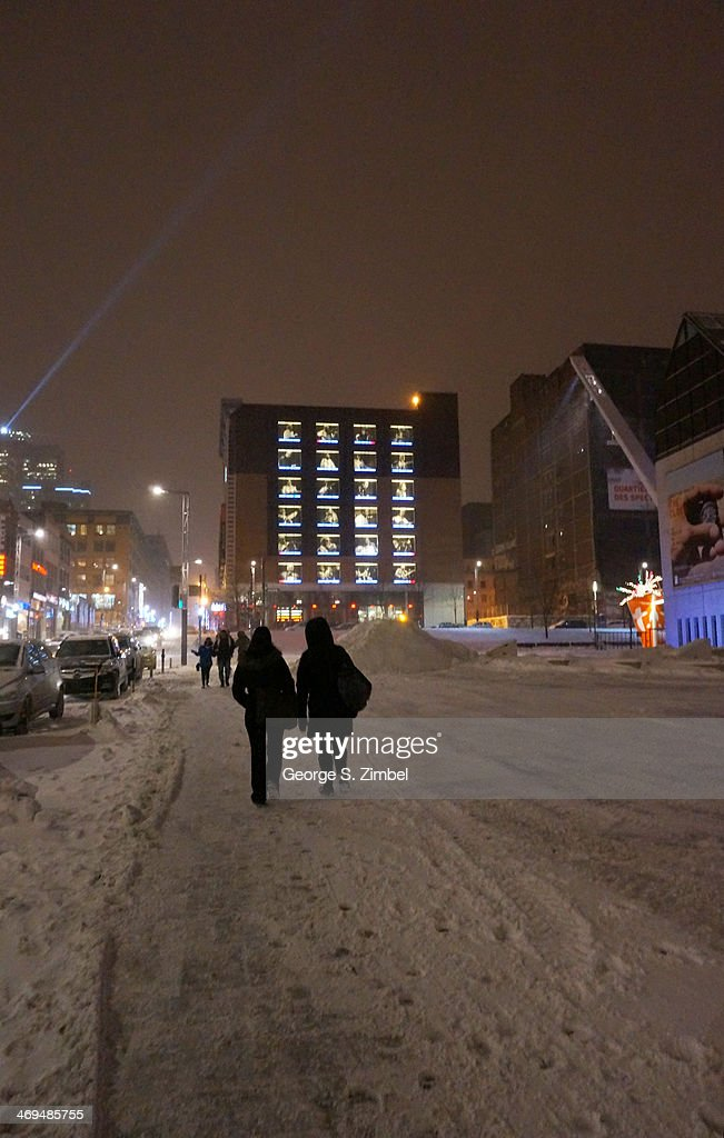 Pedestrians walks along Saint Catherine Street, Montreal, Quebec, Canada, February 5, 2014. The L'Astral Musimax concert venue is visible in the distance, its windows illumintaed with views of various musicians.