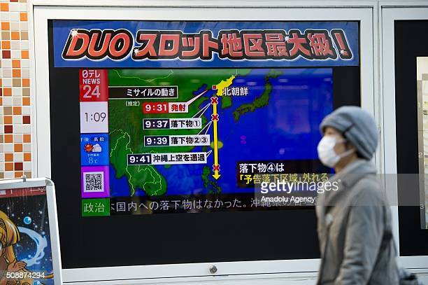 Pedestrians walks front a news channel's screen in Tokyo Japan which report about North Korea's rocket launch on February 7 2016 North Korea launched...