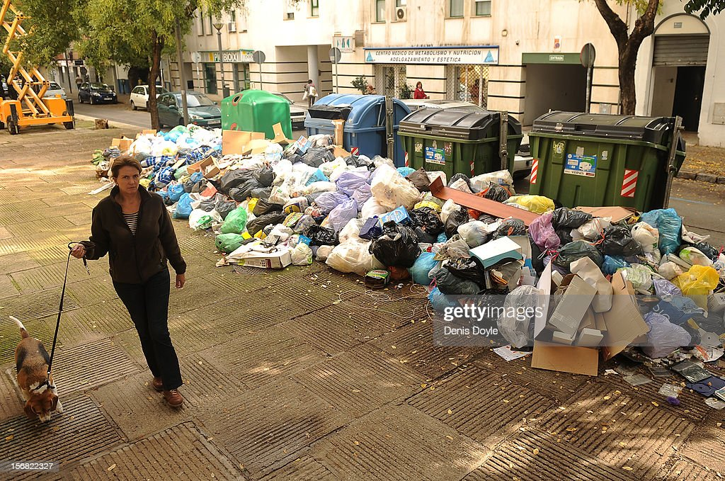 A pedestrians walks her dog past a pile of uncollected garbage during the 21st day of the garbage collectors strike on November 22, 2012 in Jerez de la Frontera, Spain. The garbage collectors will vote today on a compromise deal which saves the 123 jobs due to be cut in favour of reductions in salaries.