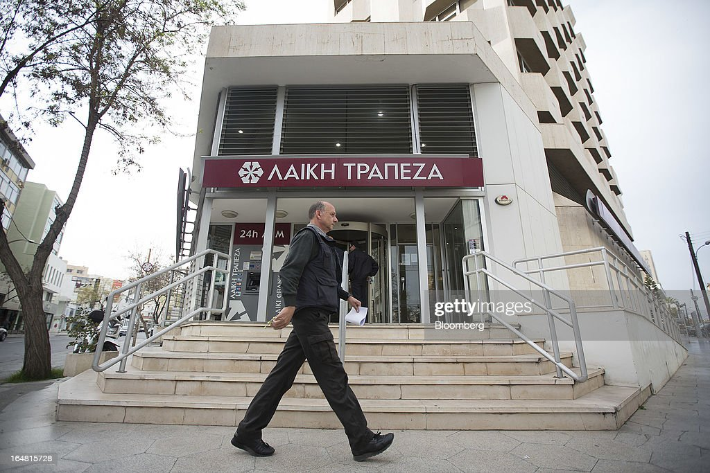 A pedestrians walks outside a branch of Cyprus Popular Bank Pcl, also known as Laiki Bank, as banks open for the first time in two weeks in Nicosia, Cyprus, on Thursday, March 28, 2013. The Central Bank of Cyprus's capital controls will include a 300-euro ($383) daily limit on withdrawals and restrictions on transfers to accounts outside the country. Photographer: Simon Dawson/Bloomberg via Getty Images