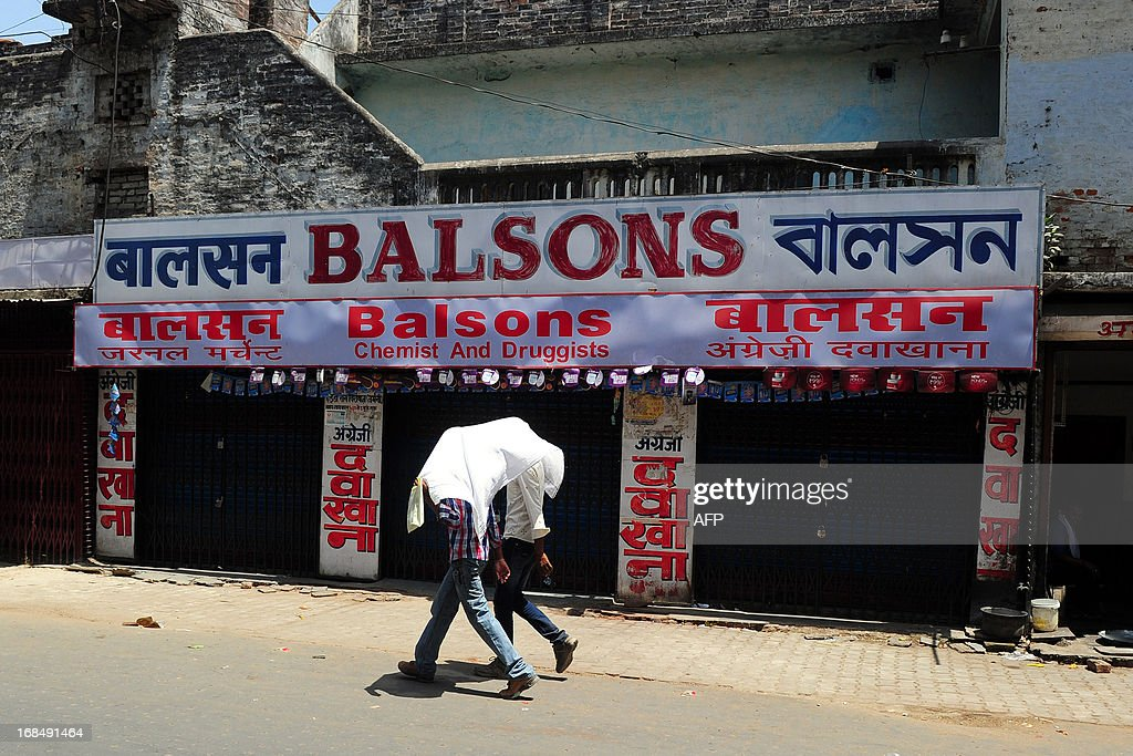 Pedestrians walks past a closed drugstore during a nationwide strike called by the All India Organisation of Chemists and Druggists Associations (AIOCDA) in Allahabad on May 10, 2013. An estimated 750,000 chemists across the country are observing the strike against government policies and their impact on traders, a report said citing a statement from the Retailers and Distributors Chemist Association (RDCA).