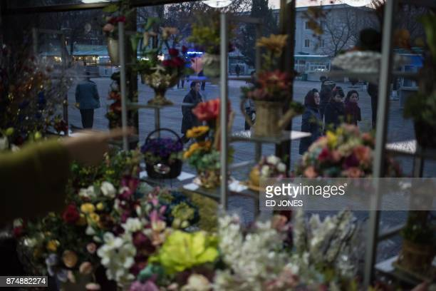 Pedestrians walks past a flower shop on Mother's Day in Pyongyang on November 16 2017 North Koreans in Pyongyang typically mark Mother's Day with...