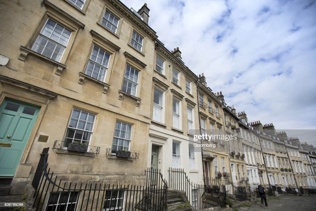A pedestrians walks past a row of terraced houses on a suburban street in Bath, U.K. on Monday, Aug. 21, 2017. U.K. property prices stagnated in July as a slump in London values spread to neighboring areas, according to theRoyal Institution of Chartered Surveyors. Photographer: Jason Alden/Bloomberg via Getty Images