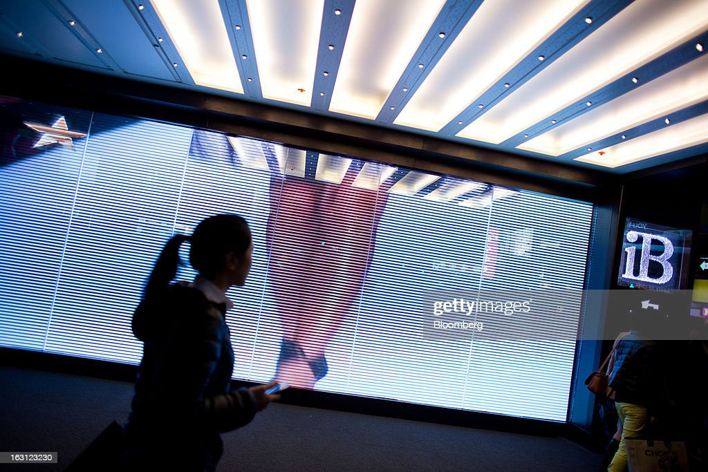 Pedestrians walks past a screen in the Causeway Bay district of Hong Kong, China, on Monday, March 4, 2013. Hong Kong's Causeway Bay overtook New York's Fifth Avenue as the world's most expensive retail location last year, with annual average shop rents reaching $2,630 per square foot at the end of June, a 35 percent increase from a year earlier, according to property broker Cushman & Wakefield Inc. Photographer: Lam Yik Fei/Bloomberg via Getty Images