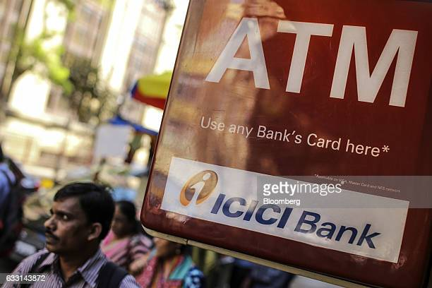 Pedestrians walks past signage for ICICI Bank Ltd automated teller machines in Mumbai India on Friday Jan 27 2017 India's Finance Ministry will...
