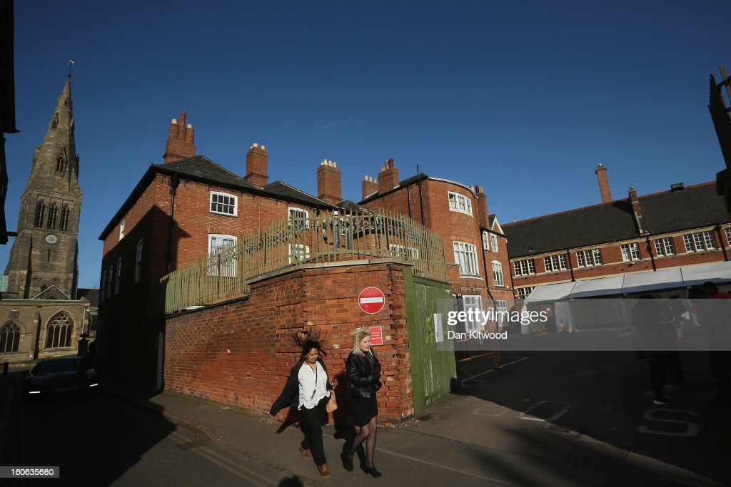 Pedestrians walks past the site (R) where the body of Richard III was discovered, on February 4, 2013 in Leicester, England. The University of Leicester has been carrying out scientific investigations on remains found in a car park to find out whether they are those of King Richard III since last September, when the skeleton was discovered in the foundations of Greyfriars Church, Leicester. King's Richard III's remains are to be interred at Leicester Catherdral.