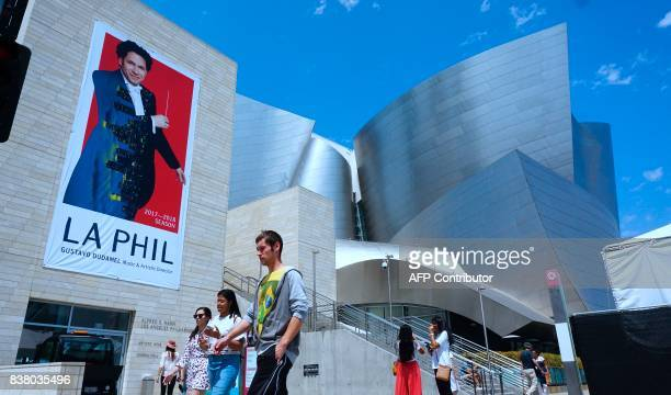 Pedestrians walks past the Walt Disney Concert Hall home to the Los Angeles Philarmonic where a banner of the Los Angeles Philarmonic Music and...