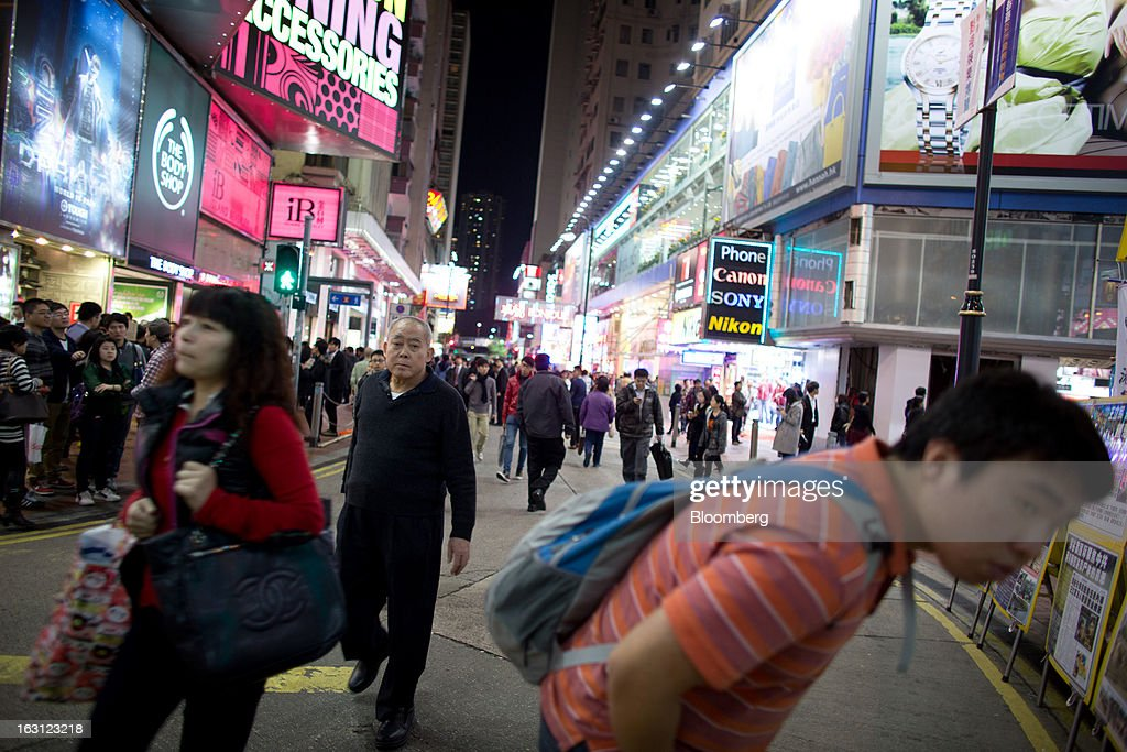 Pedestrians walks through the Causeway Bay district of Hong Kong, China, on Monday, March 4, 2013. Hong Kong's Causeway Bay overtook New York's Fifth Avenue as the world's most expensive retail location last year, with annual average shop rents reaching $2,630 per square foot at the end of June, a 35 percent increase from a year earlier, according to property broker Cushman & Wakefield Inc. Photographer: Lam Yik Fei/Bloomberg via Getty Images