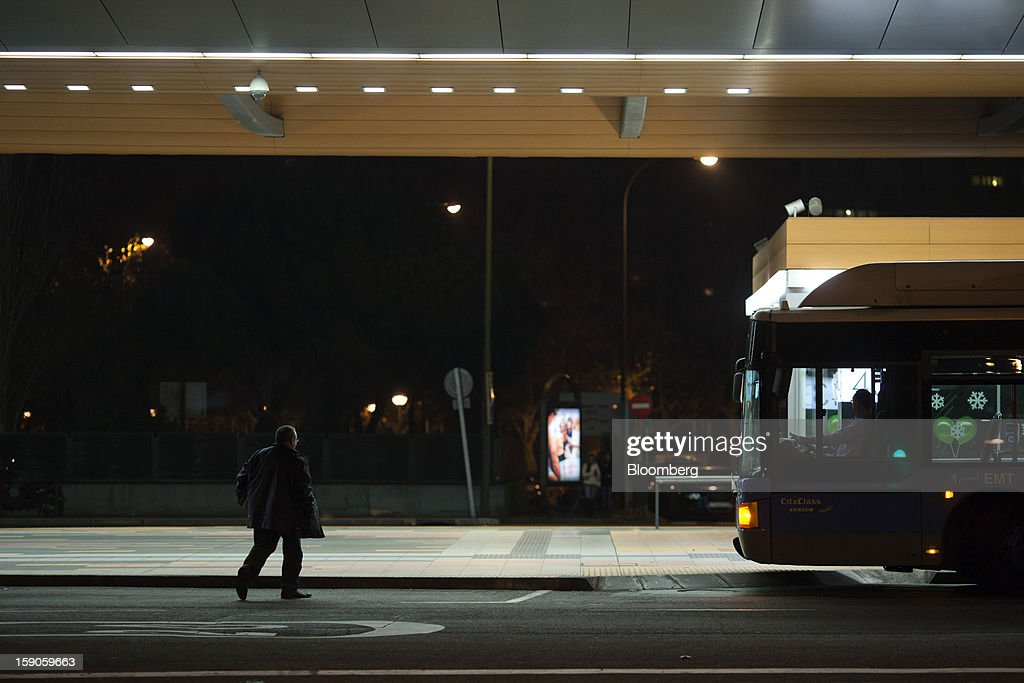 A pedestrians walks towards an urban bus on a street illuminated at night in Madrid, Spain, on Sunday, Jan. 6, 2013. In December, the Spanish parliament passed an energy law that imposed a 7 percent tax on electricity generation from Jan. 1 to plug the deficit. Photographer: Angel Navarrete/Bloomberg via Getty Images