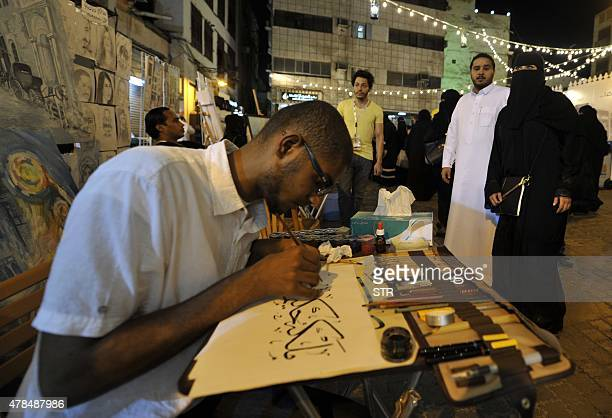 Pedestrians watch a man drawing Islamic texts in Arabic calligraphy during a festival to celebrate the Muslim holy fasting month of Ramadan in the...