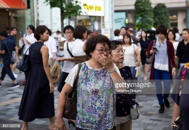 Pedestrians watch a monitor showing a news program reporting on North Korea's 6th nuclear test on September 3 2017 in Tokyo Japan South Korea Japan...
