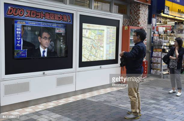 Pedestrians watch a television screen displaying Taro Kono Japan's foreign minister in a news program reporting on North Korea's missile launch in...