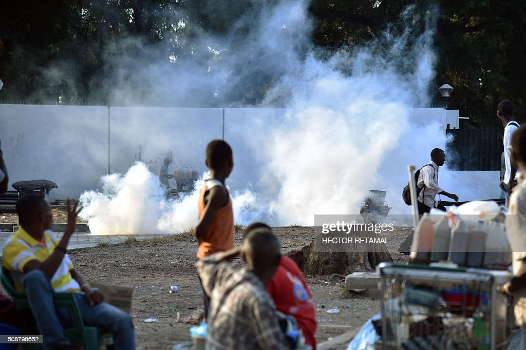 Pedestrians watch as teargas is employed during a protest by opposition demonstrators against Haitian President Michel Martelly, in Port-au-Prince, on February 6, 2016. Haitian politicians inked a last-minute agreement to install a transitional government, just hours before President Michel Martelly was scheduled to step down with no replacement in line. / AFP / HECTOR RETAMAL