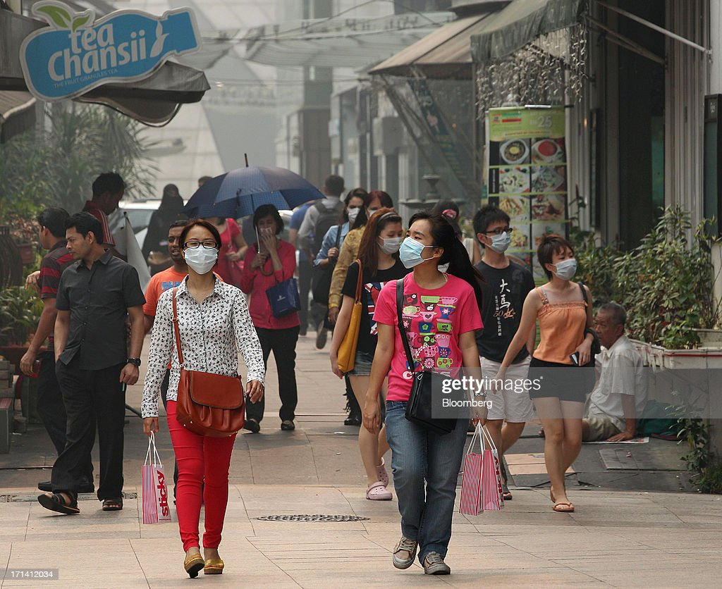 Pedestrians wear face masks as they walk along a street in Kuala Lumpur, Malaysia, on Monday, June 24, 2013. Malaysia called for a meeting of Southeast Asian ministers as early as next week after haze from illegal Indonesian forest fires reached hazardous levels in parts of the region. Photographer: Goh Seng Chong/Bloomberg via Getty Images