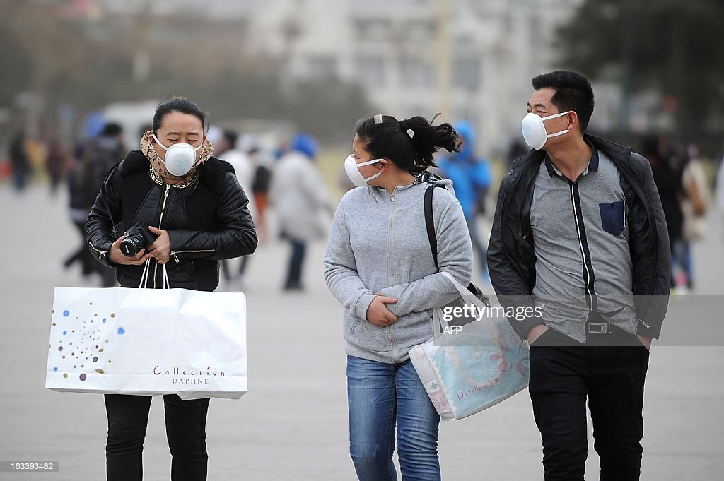 Pedestrians wear face masks as they walk in strong winds near Tiananmen Square in Beijing on March 9, 2013. Strong winds and dust storms swept the Chinese capital on March 9.