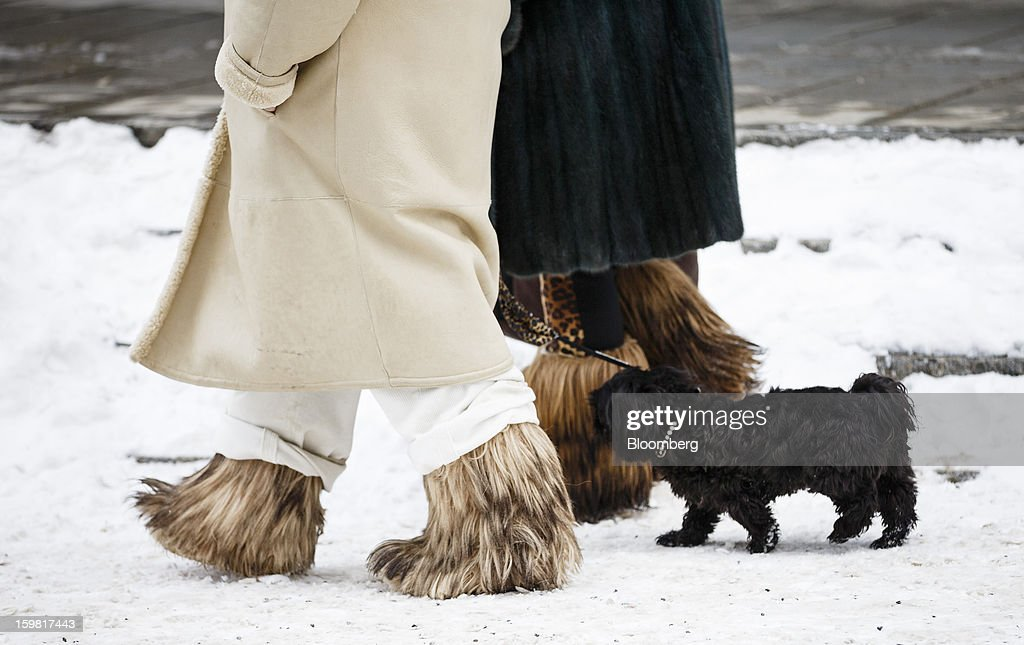 Pedestrians wear fur snow boots as they walk a dog through the snow in Gstaad, Switzerland, on Saturday, Jan. 19, 2013. Options traders are pushing the cost of bearish wagers on Swiss shares to the lowest level in almost seven years amid optimism a decline in the franc versus the euro will benefit the nation's exporters. Photographer: Valentin Flauraud/Bloomberg via Getty Images
