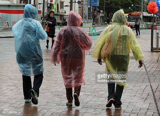 Pedestrians wear rain ponchos as they walk in the wind and rain delivered by Typhoon Vongfong on October 13 2014 in Himeji Japan According to the...