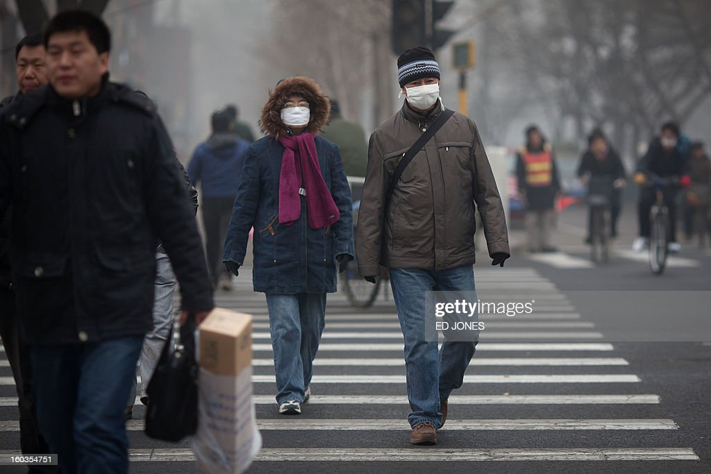 Pedestrians wearing face masks cross a road during heavily polluted weather in Beijing on January 30, 2013. Residents across huge swathes of northern China battled through choking pollution at extreme levels, as Beijing was plunged into toxic twilight for the fourth time this winter. AFP PHOTO / Ed Jones