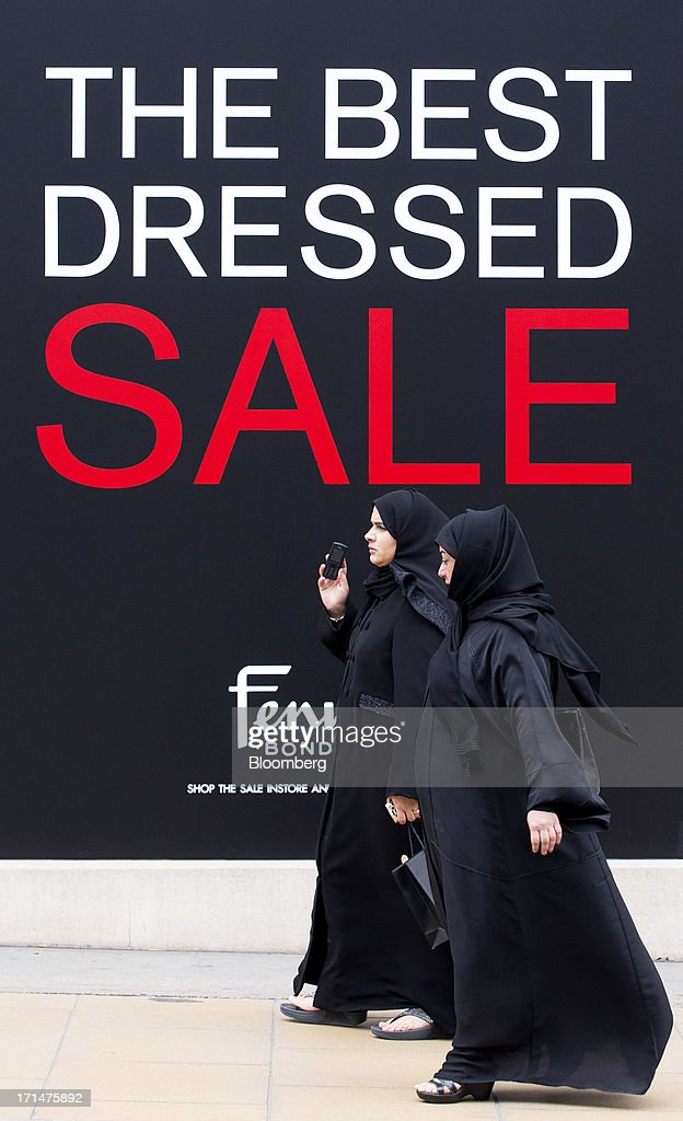 Pedestrians wearing hijabs pass a sale sign outside a Fenwick department store on New Bond Street, in London, U.K., on Monday, June 24, 2013. Bank of England Governor Mervyn King said the global economic recovery is at risk of further setbacks and central banks are a long way off tightening monetary policy. Photographer: Jason Alden/Bloomberg via Getty Images
