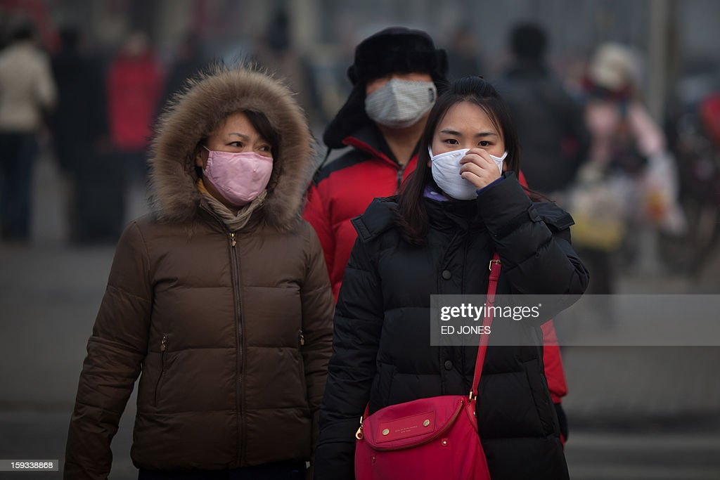 Pedestrians wearing masks wait to cross a road during severe pollution in Beijing on January 12, 2013. Air quality data released via the US embassy twitter feed recorded air quality index levels so hazardous that they were classed as 'Beyond Index'. By 4pm the particle matter (PM) 2.5 figure was 728 on a scale that stops at 500 at which point the US embassy website advises against all outdoor activity. AFP PHOTO / Ed Jones