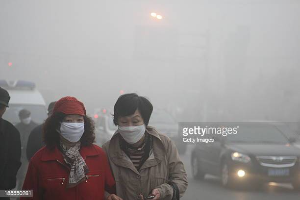 Pedestrians wearing masks walk along a road as heavy smog engulfs the city on October 22 2013 in Harbin China Expressways schools and an airport...