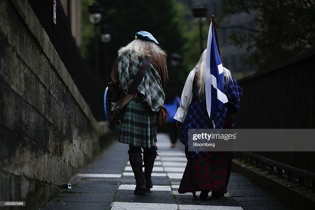 Pedestrians wearing traditional Scottish clothes, including a tartan kilt, carry a St. Andrew's or Saltire flag, the national flag of Scotland, as they walk in Edinburgh, U.K., on Tuesday, Sept. 16, 2014. The battle over Scotland's future in the U.K. entered the final day of campaigning with the pro-independence side saying it had the momentum to win the ballot and the Better Together 'no' camp urging voters not to use it as a protest. Photographer: Simon Dawson/Bloomberg via Getty Images