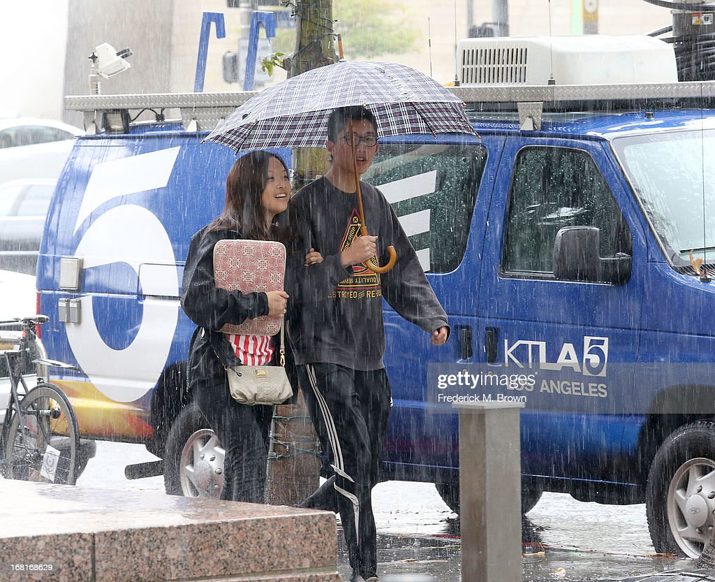Pedestrians with an umbrella during a heavy rain storm walk past a news van parked outside of the courthouse for the Jackson vs AEG Court Case on May 6, 2013 in Los Angeles, California. o