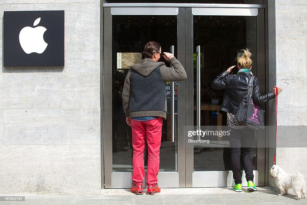 Pedestrians with their pet dog stop to look through the door and into the new Apple Inc. store ahead of the opening on Kurfurstendamm Street in Berlin, Germany, on Wednesday, May 1, 2013. The Berlin Apple Inc. store is the company's 11th in the country, but the first in Germany's capital city. Photographer: Krisztian Bocsi/Bloomberg via Getty Images