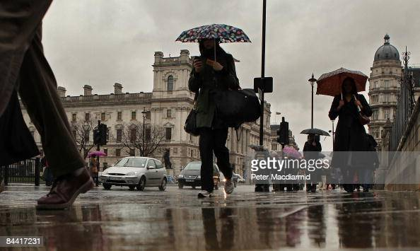 Pedestrians with umbrellas walk near the Treasury building on January 23 2009 in London Statistics released today show that the United Kingdom is...