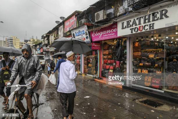 Pedestrians with umbrellas walk past leather goods stores in the Dharavi area of Mumbai India on Tuesday July 18 2017 India's new goods and services...