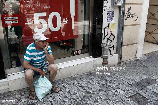 A pedetrian sits outside a store advertising 50% discounts during the summer sales in Athens Greece on Monday July 13 2015 Greece has been in...