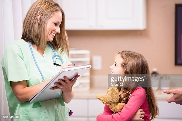 Pediatrician doctor writes notes, medical chart. Girl patient. Doctor's office.