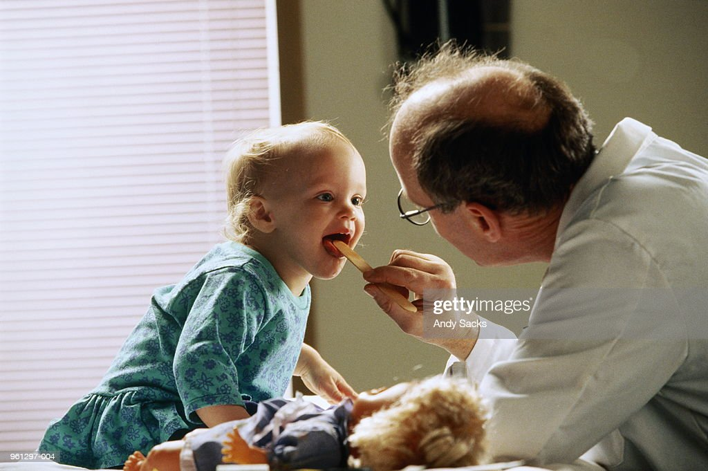 Pediatrician examining girl (21-24 months) in surgery : Stock Photo