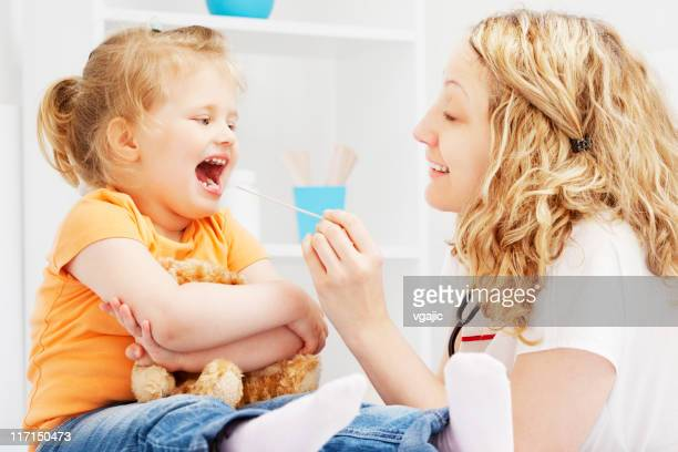 Pediatrician friendly checking little girl throat
