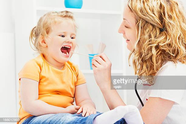 Pediatrician friendly checking little girl throat
