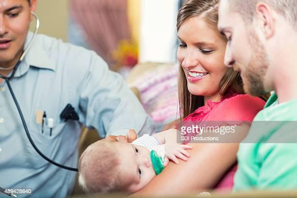 Pédiatre rendre visite à domicile pour nouveau-né patient avec les parents